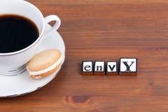 Кофейная чашка на деревянном столе и тексте - завистливости стоковое фото rf