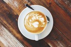 Кофейная чашка на деревянном столе, художническом фото Стоковая Фотография RF
