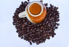 Кофейная чашка на кофейных зернах изолированных на белизне Стоковая Фотография