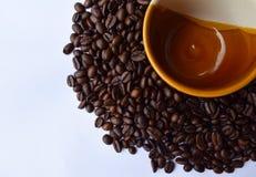 Кофейная чашка на кофейных зернах изолированных на белизне Стоковое Фото