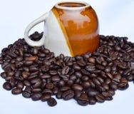 Кофейная чашка на кофейных зернах на белизне Стоковые Фото