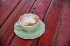 Кофейная чашка на красной таблице Стоковое Фото