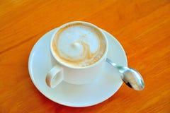 Кофейная чашка на предпосылке деревянного стола Стоковые Фотографии RF
