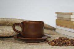 Кофейная чашка на burlac с предпосылкой книги и нерезкости стоковые изображения