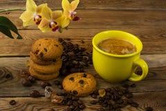 Кофейная чашка, печенья и желтая орхидея Стоковое фото RF