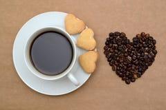 Кофейная чашка, печенья и кофейные зерна в форме сердца Стоковые Фото
