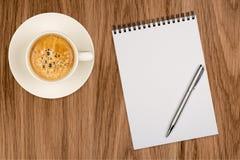 Кофейная чашка, спиральная тетрадь и ручка на деревянном столе Стоковая Фотография