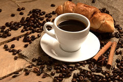 Кофейная чашка с кофейными зернами круассаном, циннамоном на bagging и Стоковая Фотография