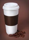 Кофейная чашка с кофейными зернами на коричневой предпосылке Стоковое Фото