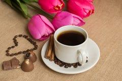 Кофейная чашка с кофейными зернами на мешковине и розовых тюльпанах стоковая фотография