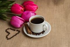 Кофейная чашка с кофейными зернами на мешковине и розовых тюльпанах стоковая фотография rf