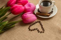 Кофейная чашка с кофейными зернами на мешковине и розовых тюльпанах стоковое фото