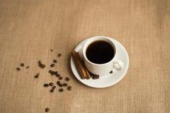 Кофейная чашка с кофейными зернами на мешковине стоковое фото