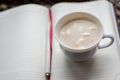 Кофейная чашка с пеной на предпосылке книги с чистыми страницами Стоковые Фото