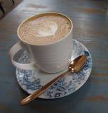 Кофейная чашка с поддонником и ложкой чая на таблице Стоковая Фотография RF