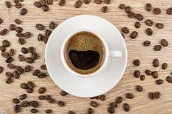 Кофейная чашка с поддонником и разбросанными кофейными зернами Стоковые Фото