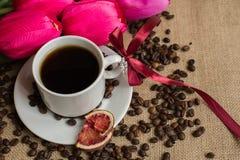 Кофейная чашка с сырцовыми фасолями на мешковине с розовыми тюльпанами стоковое изображение