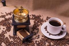Кофейная чашка с сырцовыми фасолями на мешковине с точильщиком стоковые изображения rf