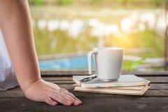 Кофейная чашка с тетрадью на деревенской деревянной таблице Стоковая Фотография RF