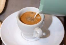 Кофейная чашка эспрессо и лить молоко в чашку на столе в ресторане стоковое фото rf