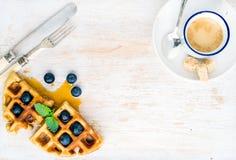 Кофейная чашка эспрессо, мягкие бельгийские waffles с свежими голубиками и сироп marple на белизне покрасили деревянную доску све Стоковые Фото