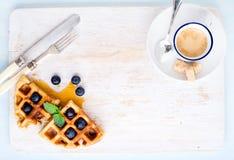 Кофейная чашка эспрессо, мягкие бельгийские waffles с свежими голубиками и сироп marple на белизне покрасили деревянную доску све Стоковое фото RF