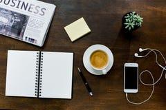Кофейная чашка, smartphone с пустым экраном и наушниками, тетрадь с ручкой, газета и суккулентный завод в баке Стоковое фото RF