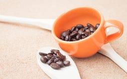 Кофейное зерно в чашке и ложке Стоковое Фото