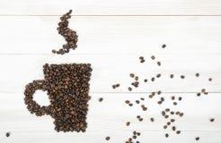 Кофейные зерна взгляд сверху делая форму из чашки на деревянной поверхности Стоковые Фото