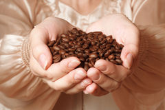 Кофейные зерна в женских руках Стоковая Фотография RF