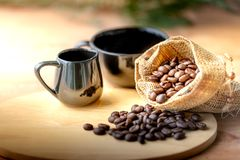 Кофейные зерна в мешке около черного керамического стекла дальше стоковая фотография