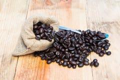 Кофейные зерна в мешочке из ткани с ложкой Стоковые Фотографии RF