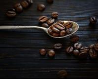 Кофейные зерна в ложке металла на темной деревянной предпосылке стоковое фото