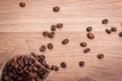 Кофейные зерна в стекле и на деревянном столе Стоковое Фото