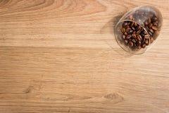Кофейные зерна в стекле на предпосылке деревянных доск Стоковое Фото