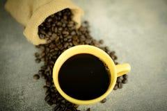 Кофейные зерна в сумке и кофейной чашке Стоковое Изображение