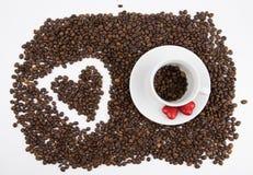 Кофейные зерна в чашке на белой предпосылке стоковые изображения