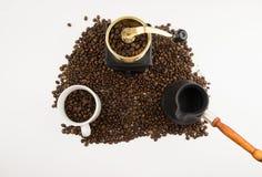 Кофейные зерна в чашке с точильщиком на белой предпосылке стоковые изображения