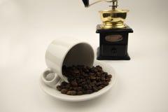 Кофейные зерна в чашке с точильщиком на белой предпосылке стоковые изображения rf