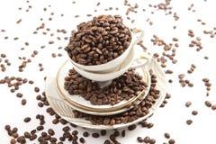 Кофейные зерна в чашке фарфора на белой предпосылке Стоковые Изображения RF