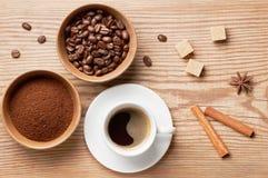 Кофейные зерна, земной кофе и чашка кофе на деревенском деревянном столе украсили специи, сахар и кофейные зерна, взгляд сверху Стоковые Фотографии RF