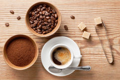 Кофейные зерна, земной кофе и чашка кофе на деревянном столе с оборудованием и ингридиентами, взгляд сверху Стоковое Изображение