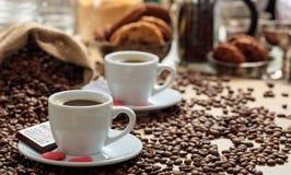 Кофейные зерна из мешка и 2 чашек кофе Стоковое фото RF