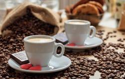 Кофейные зерна из мешка и 2 чашек кофе Стоковая Фотография RF