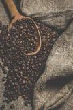 Кофейные зерна и деревянная ложка на традиционной ткани мешка Стоковое Изображение RF