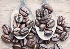 Кофейные зерна и ложка кофе на деревянной предпосылке Стоковые Изображения