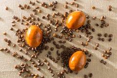 Кофейные зерна и пасхальные яйца, покрашенные с кофе на предпосылке мешковины Стоковая Фотография RF