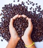 Кофейные зерна и рука Стоковая Фотография