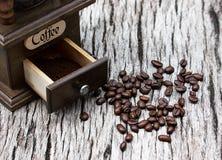 Кофейные зерна и точильщики на старых деревянных досках стоковое изображение rf