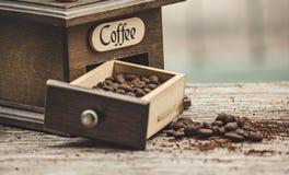 Кофейные зерна и точильщик на деревянном поле стоковые фото